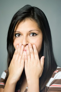 Woman with black hair covering her mouth with her hands