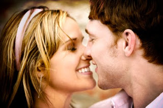 young couple smiling while about to kiss