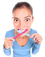 Woman brushing her teeth with two toothbrushes