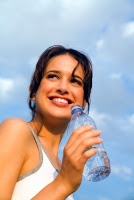 Woman smiling holding water bottle with clouds in the background