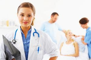 Woman doctor looking at camera while nurses help patient in the background