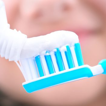 toothpaste being squeezed onto a toothbrush