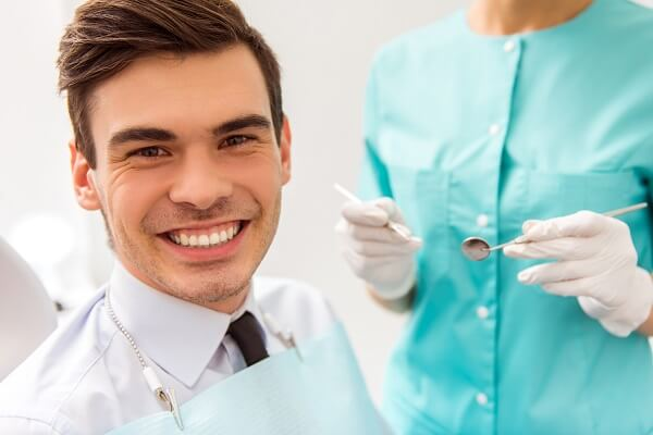 A man smiling during his appointment with his dental hygienist